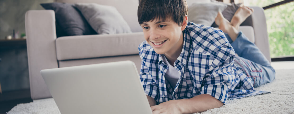 photo of teen boy on the floor doing online school, remote learning, on a laptop