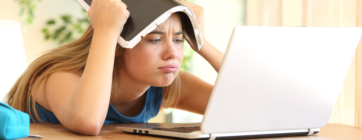 teen student struggling with online school, notebook on her head at a table at home in front of a laptop