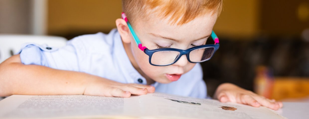 Boy with down syndrome with big glasses reading book, homeschool, special education