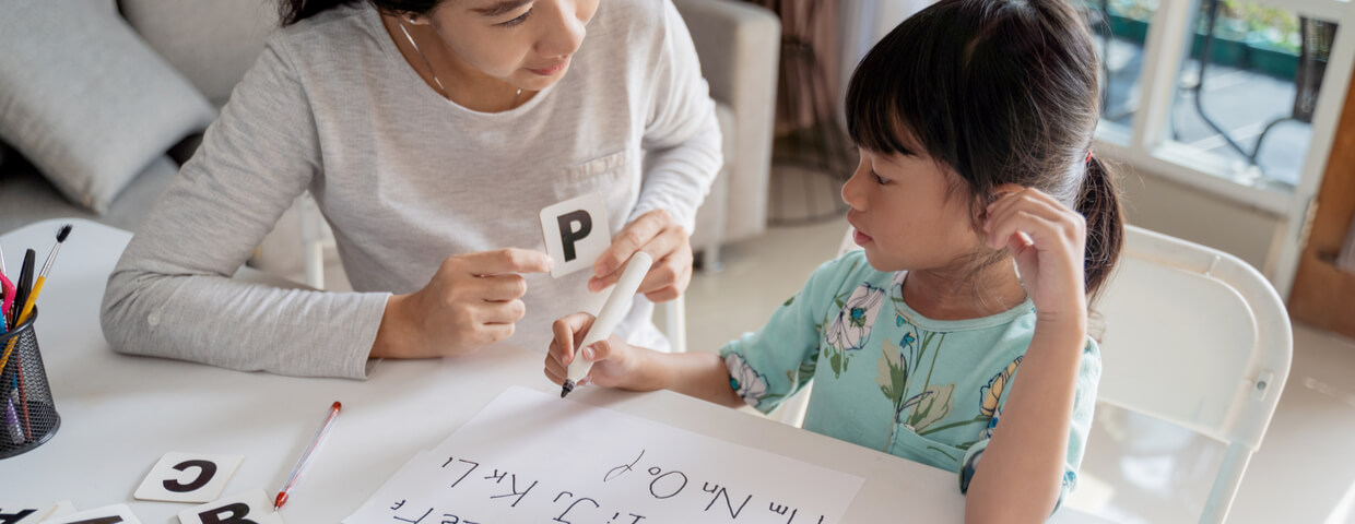 mother and daughter learning to read and write letter at home together. homeschooling activity