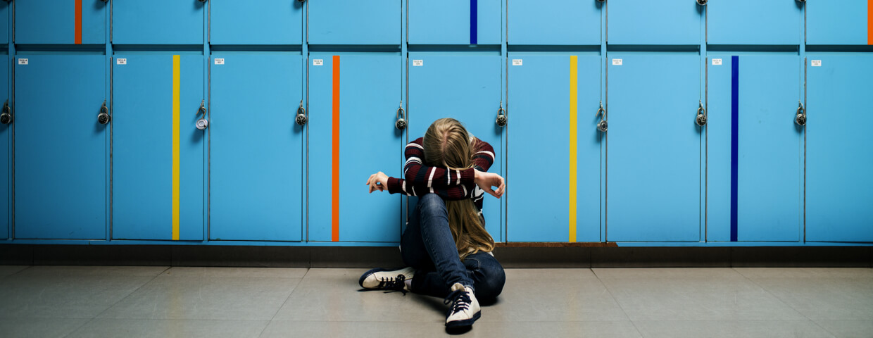 student sitting alone at lockers, young girl with head down at school alone, bullying concept,