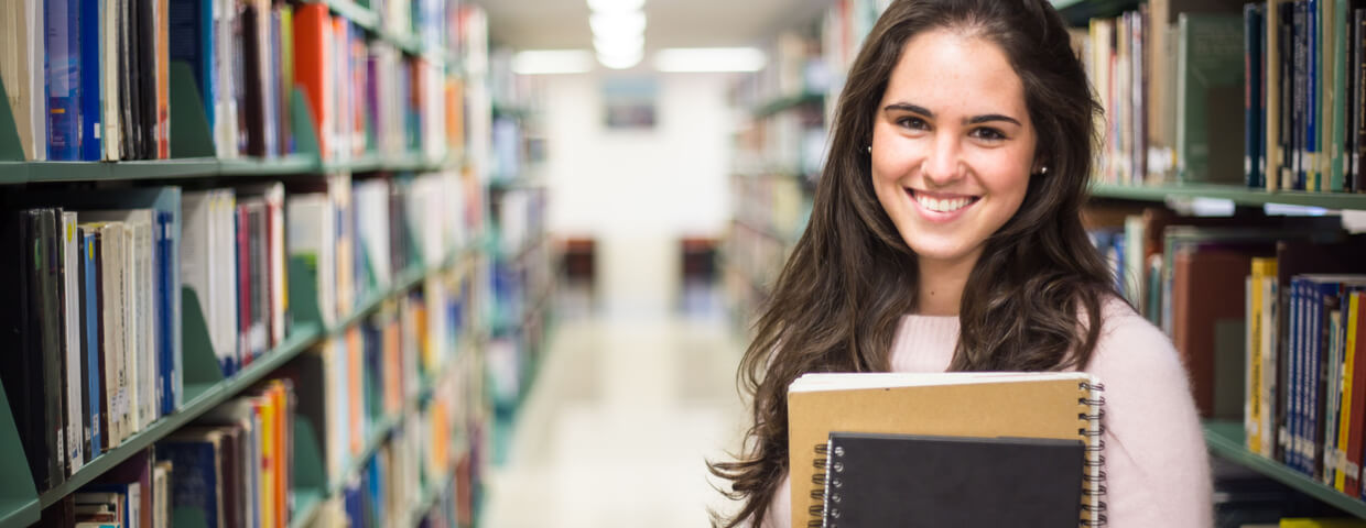 female student with books working in a high school library, dual-enrollment concept