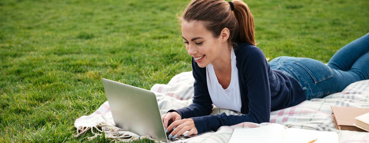 smiling teen student girl doing homework on laptop computer while lying on the grass at park, summer school