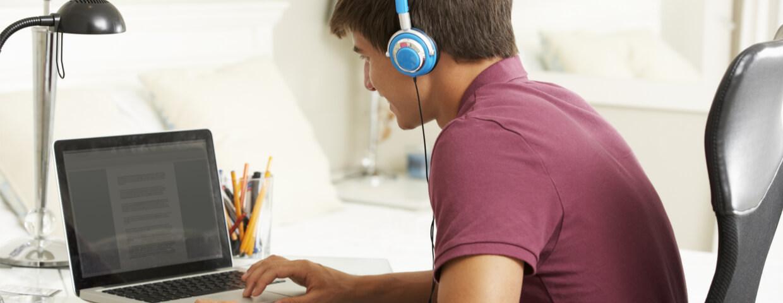 Teenage Boy Studying At Desk In Bedroom Wearing Headphones, Homeschooling concept